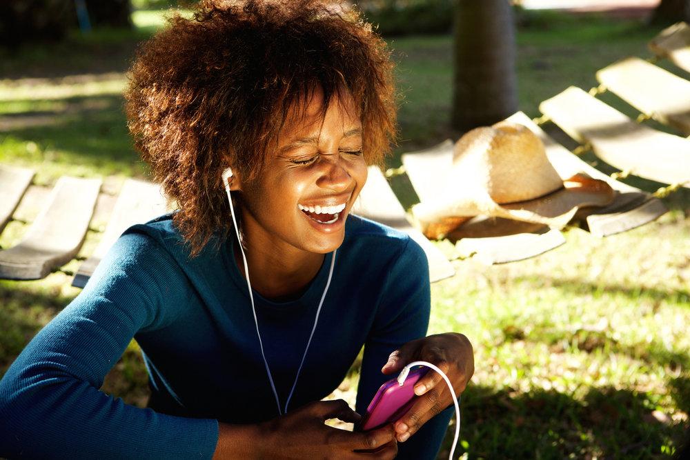 Black woman listening podcast phone earphones.jpg