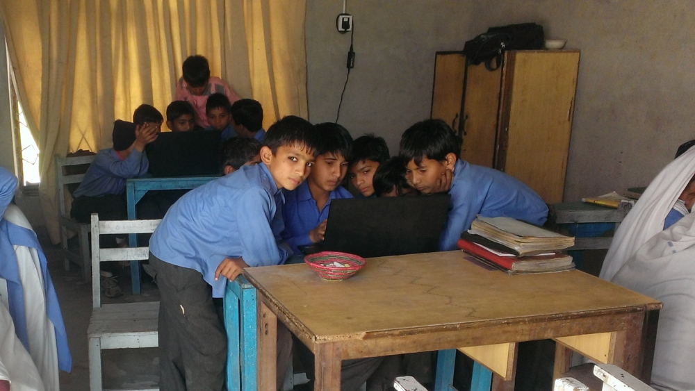 The students of Grade 5 are teaching super-excited students of Grade 4 how to click and move their fingers on mouse pad. To practice this, the children are using Windows Paint to make colored shapes on window's paint.