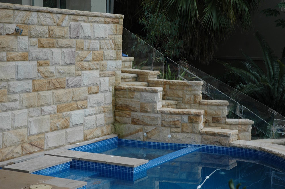 Artistry in sandstone light-medium brown rockfaced cladding, steps and pool surrounds retailing walls (11).JPG