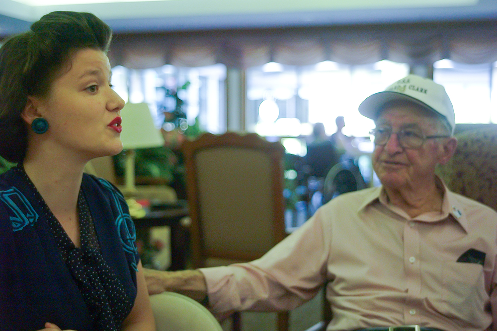 "Faith sang everywhere we went. Here she is singing ""White Cliffs of Dover"" to WWII Veteran Armand Carlucci. It was so wonderful to watch the veteran's faces as she sang the songs of their time. Often times, they would join in with her."
