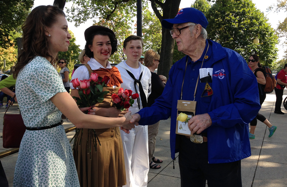 Madisson shakes the hand of WWII veteran Bill Marx from Honor Flight Dallas/Fort Worth