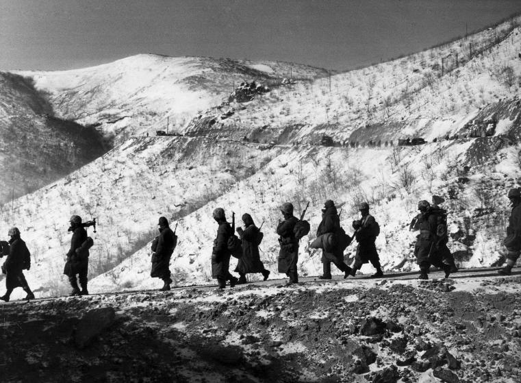"""American Marines march down a canyon road dubbed ""Nightmare Alley"" during their retreat from Chosin Reservoir, Korea."" Photo by David Douglas Duncan"