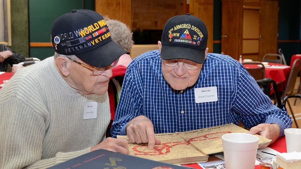 Two WWII veterans go over a European Theatre map. (Photo credit: Joe Schneider)