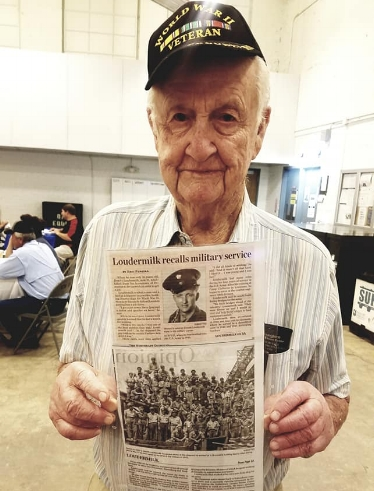 Local veteran, Dewitt Loudermilk holding a newspaper clipping about his service as an Engineer in WWII.