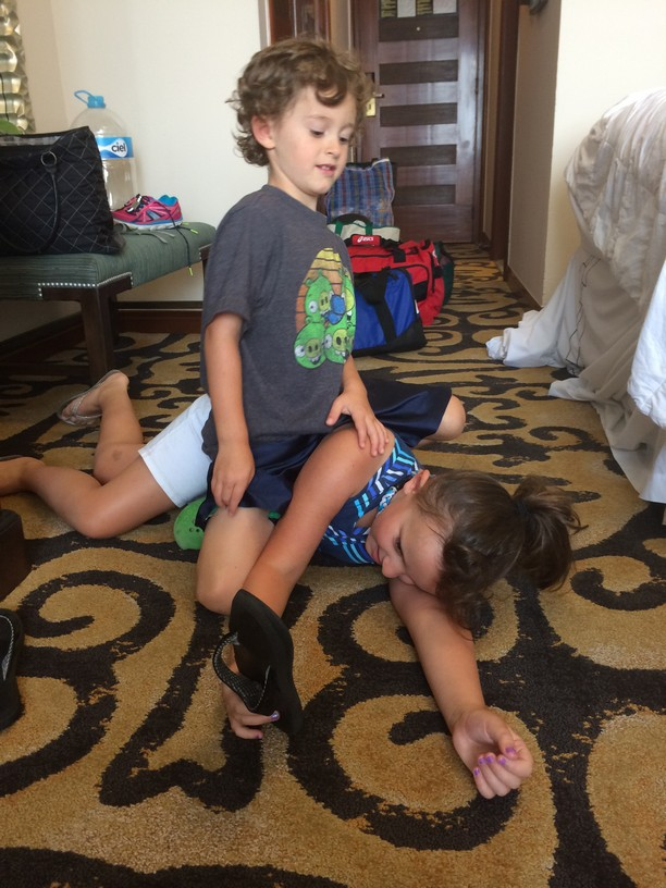 Elle and Tag wrestle in the hotel room