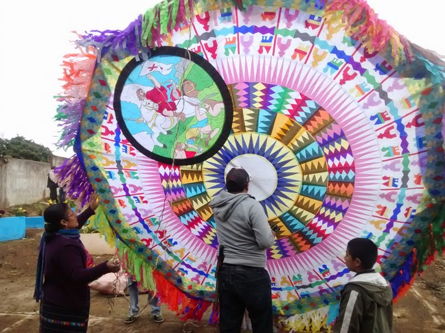 Here is a family getting ready to fly their medium size kite. The father is poking a hole in the center to thread rope through the middle.