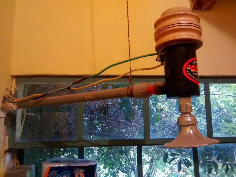 No need for a hot water heater to take warm showers with this inline electrical hot water heater (note the string holding it up).