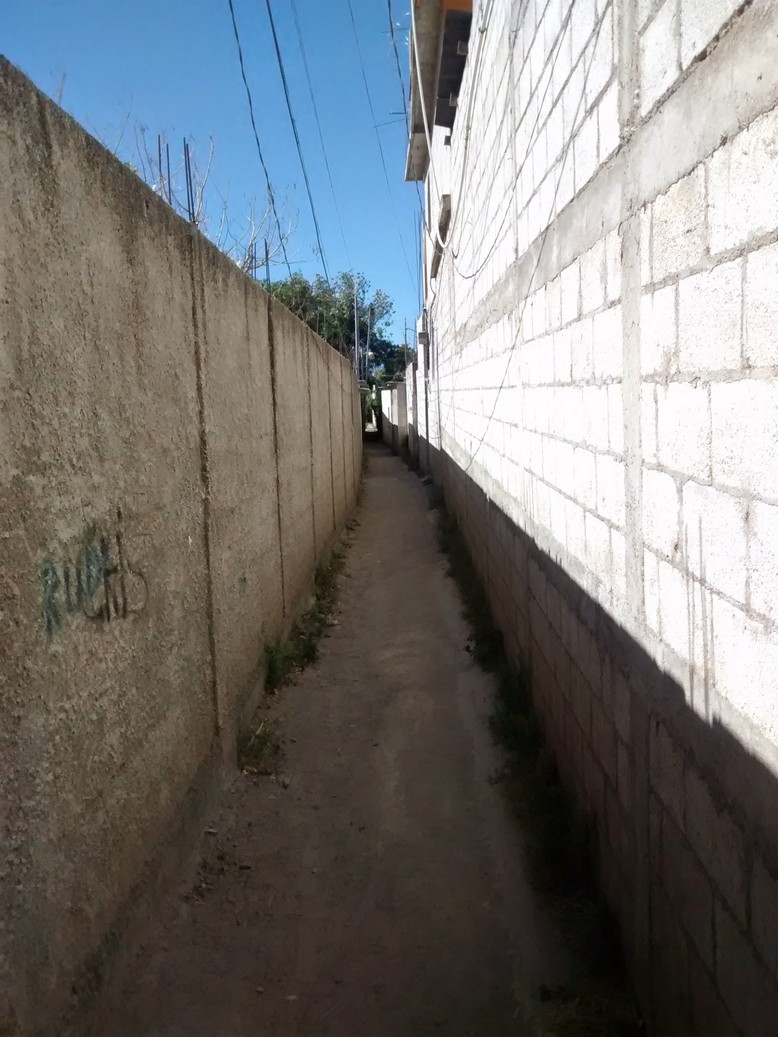 This alley is narrow, has an uneven dirt floor, barbwire along parts of the side, smells like dog poop, is quite long with no other real entry and exit points so one might conclude it is not safe.