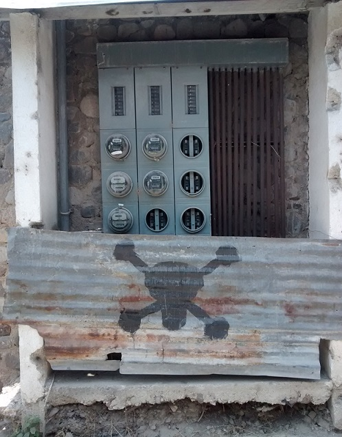 Electrical cables, panels and meters can be expensive to secure. Here the electric company warns you to stay away by using a piece of corrugated metal with a skull and cross bones painted on it.
