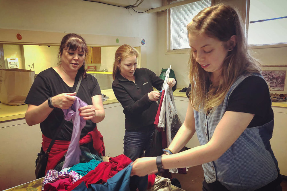 A trio of Friendly Exchange volunteers help sort and hang incoming clothing items so that you can get out there and shop for new threads faster.