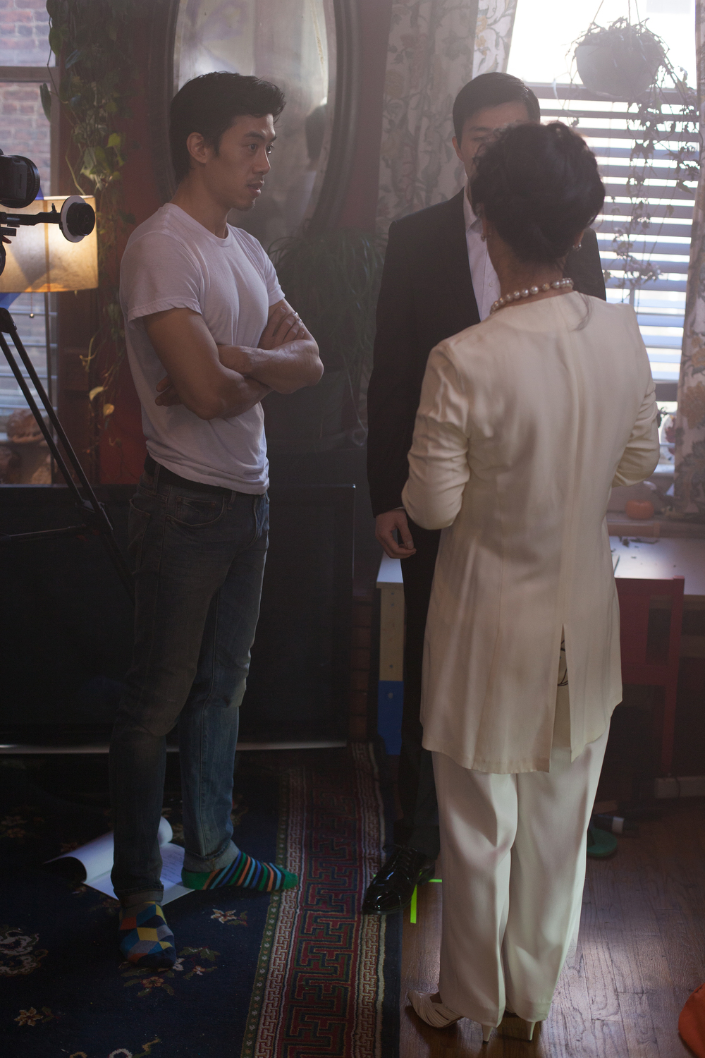 Director Leon Le rehearsing a scene with the actors before a take.