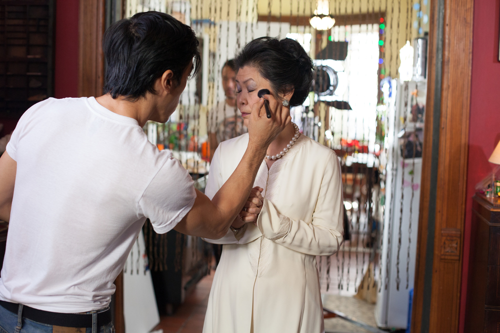 Hands on. Director Leon Le is touching up Mrs. Huang's make-up before a take.
