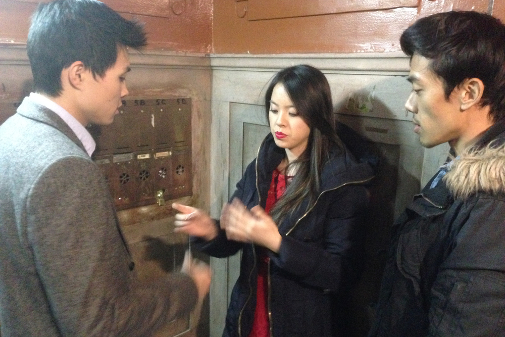 Director Leon Le blocking the scene with actors Zilong Zee and Charis Chu before a take.