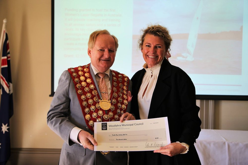 Woollahra Mayor,Peter M Cavanagh presents Secretary Alexander with a Community Grant for the Double Bay Sailing Club Women's Laser Regatta.