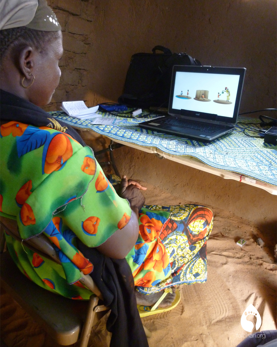 A woman performs an eye-tracking trial for sanitation and hygiene in a traditional mud brick home.