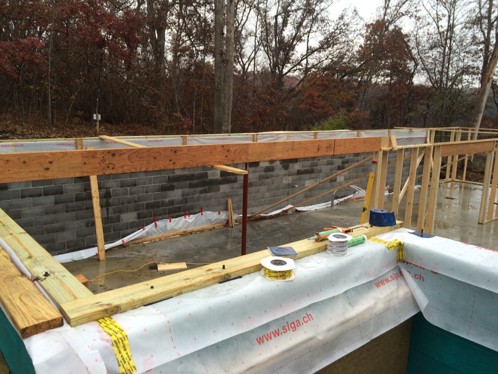 CMU Block air barrier is kept long, ready to overlap and be taped to plywood sheathing.