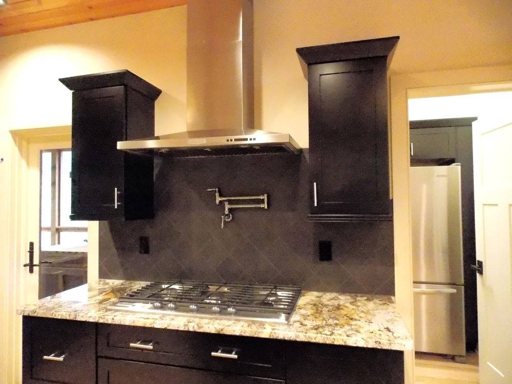 Kitchen features custom cabinetry, high end appliances, granite counter tops, and tile back splash