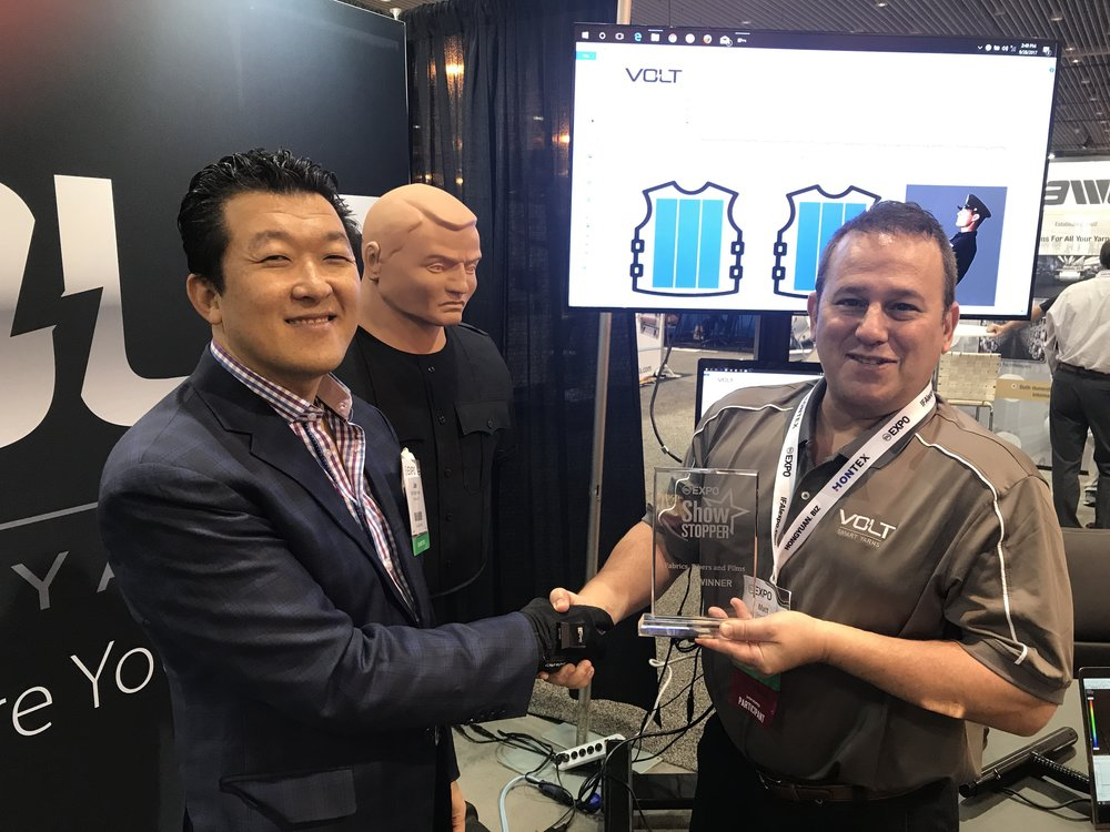 Dr. Jae Son, PPS Founder & CEO, and Matt Kolmes, Supreme Corporation CEO, shaking hands with the award.