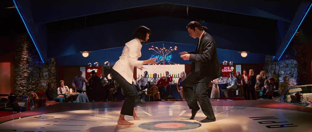 Title: Pulp Fiction  Director: Quentin Tarantino  Year: 1994  Track: You never can tell (Chuck Berry)   https://www.youtube.com/watch?v=RoDPPgWbfXY