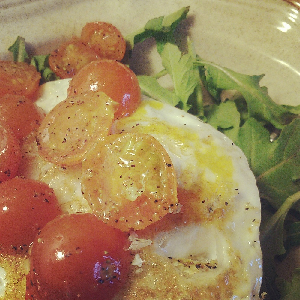sauteed cherry tomatoes with fried eggs and arugula