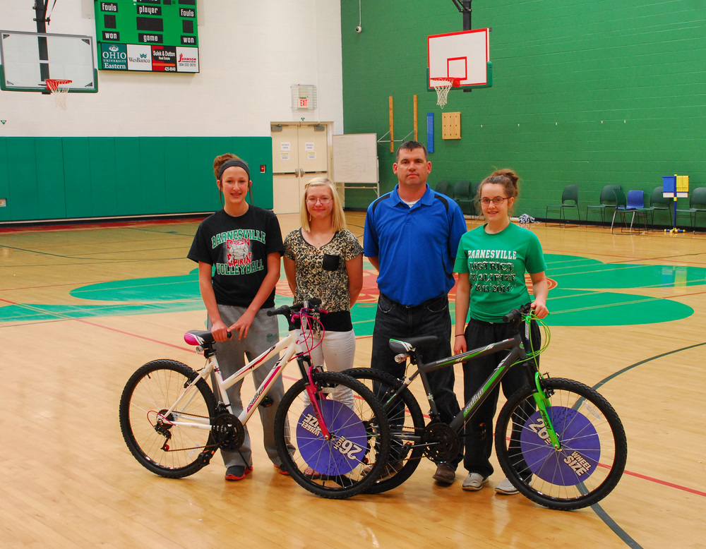 "Barnesville Middle School student volunteers, from left, Alle Sinisgalli, Casey Betts and Alayna Willis, accept two bicycles donated by Jeremy Detling, third from left, on behalf of Williams Field Services Group and their community support program. The bikes will be raffled as part of BMS's annual ""Cutting Class for a Cure"" event to raise money for 3Cs Cancer Support Group."