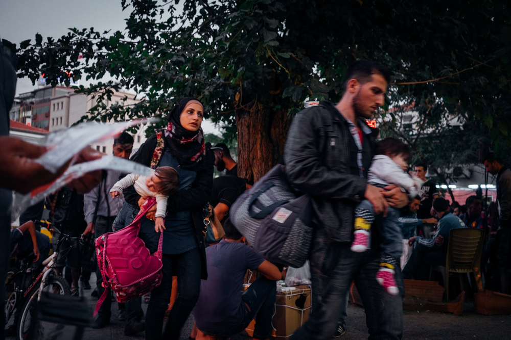 A young couple and their children rushing across Basmane Square, Izmir, a Turkish hub for refugees and smugglers alike. In this small square close the the main train station refugees and migrants connect with a smuggler to pay for a boat ride across the Aegean Sea. Boat rides were around $1,500 all through the summer of 2015. Sept 29, 2015.