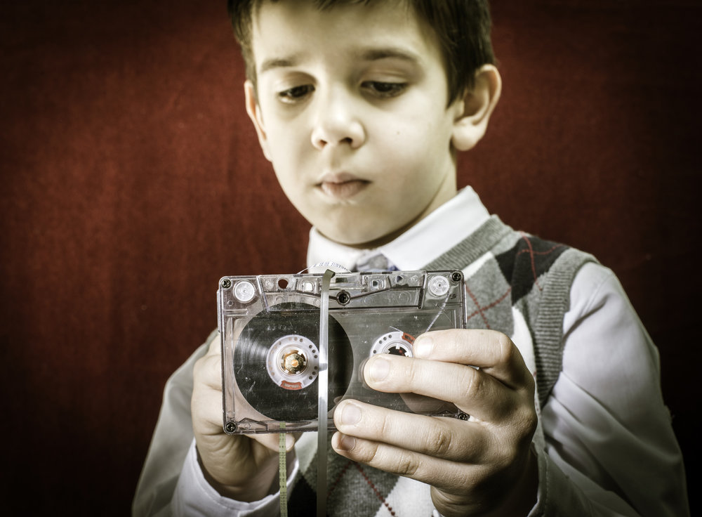photodune-6933812-rolled-cassette-strip-with-a-pencil-boy-hold-cassette-tape-l.jpg