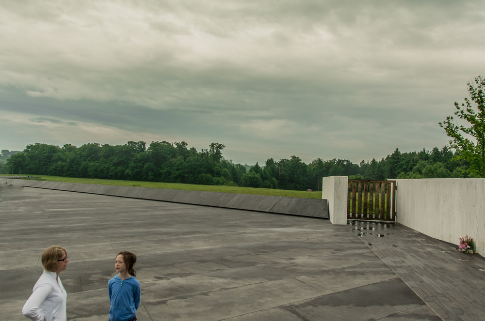 I love this picture.  Kim and MK discussing 9/11 at the Flight 93 Memorial.  The black low diagonal wall you see is where you stand to look over the crash site.  The white higher wall to the right has names of those who died in the crash.  The white wall is exactly aligned with the flight path.  The wood gate is what you look through to see the boulder in the distance (it's the small bump in the grassy field).  The boulder is the spot of impact.