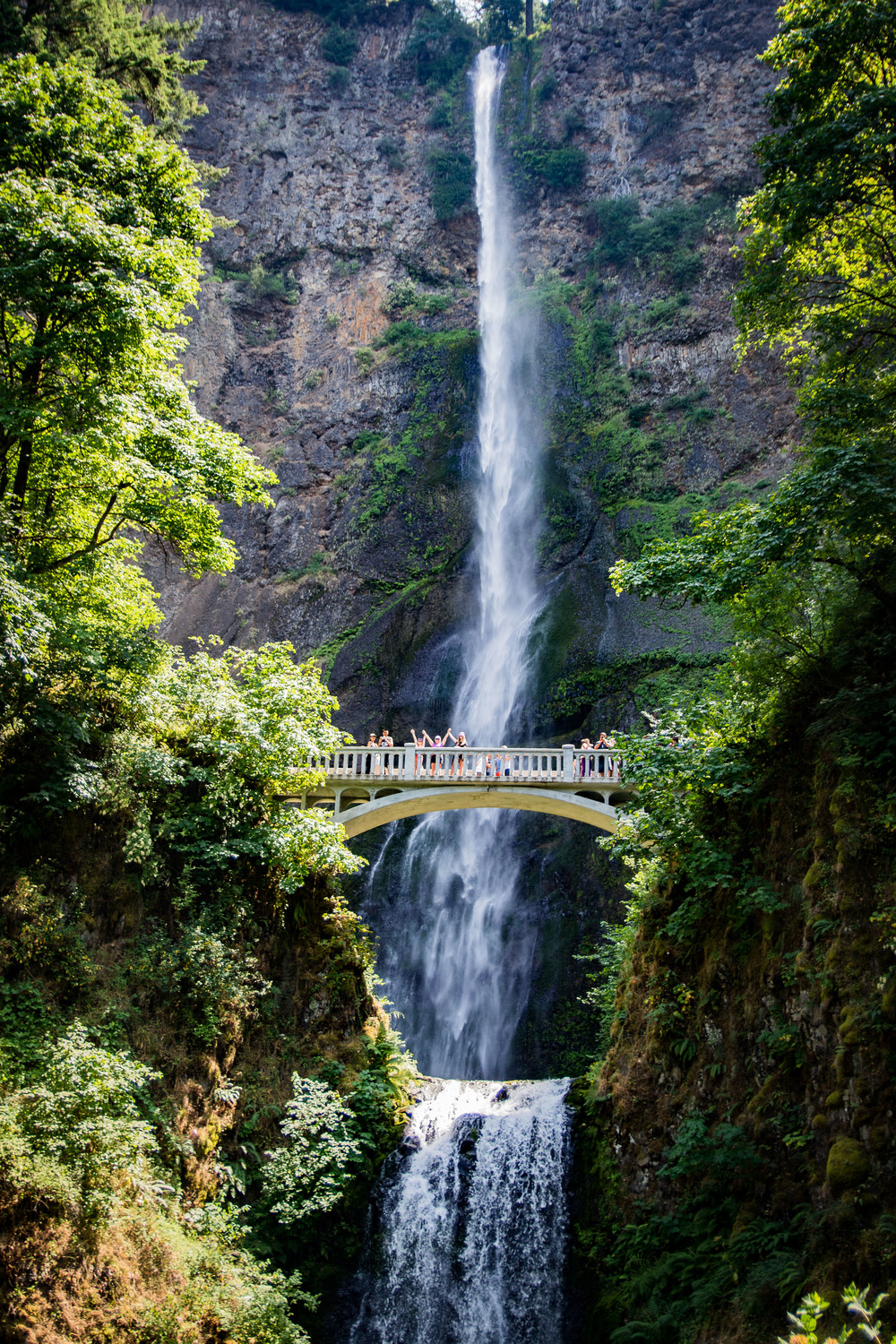 Multnomah Falls, Columbia River Gorge Area, OR. Kim, Mag and MK are on the bridge with their hands raised.