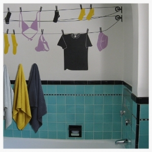 A deco-era turquoise bathroom was lovingly restored. Re-grouting, repairing cracked tile, and playfully updated with modern wall art. Eclectic colors are accentuated for a vintage-fun child's bathroom.