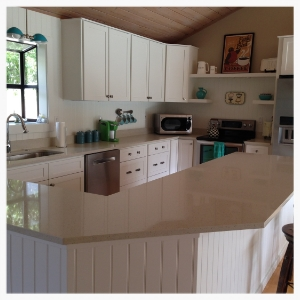 Guest house kitchen gets updated on a budget with painted cabinet bases, new white cabinet doors and drawers, and white bead board applied to the  island and  backsplash. Light quartz freshens the counter tops.
