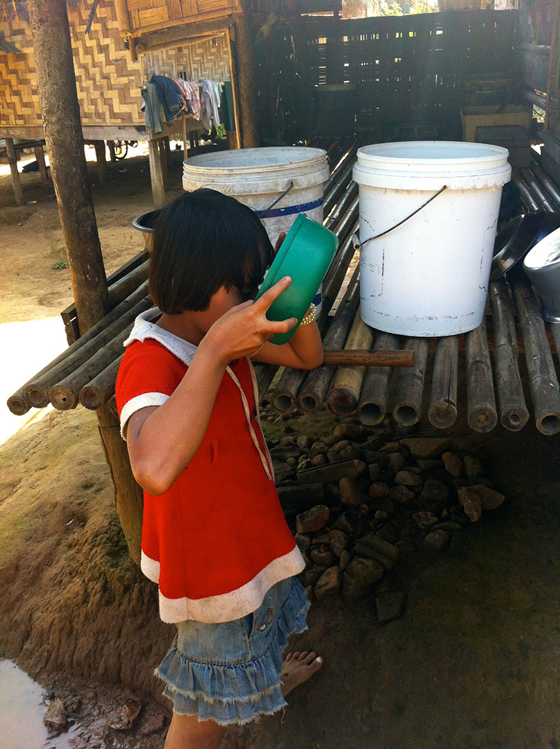 A child drinking water from a water storage container (Ban Mai community)