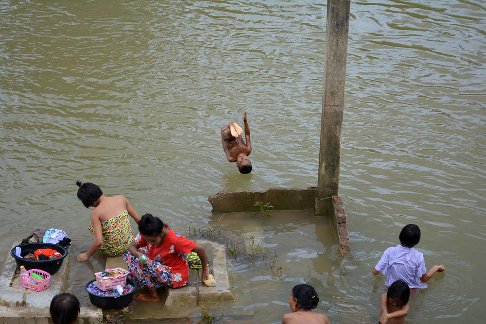 The locals washing and playing in the river that flows by Ban Mai.