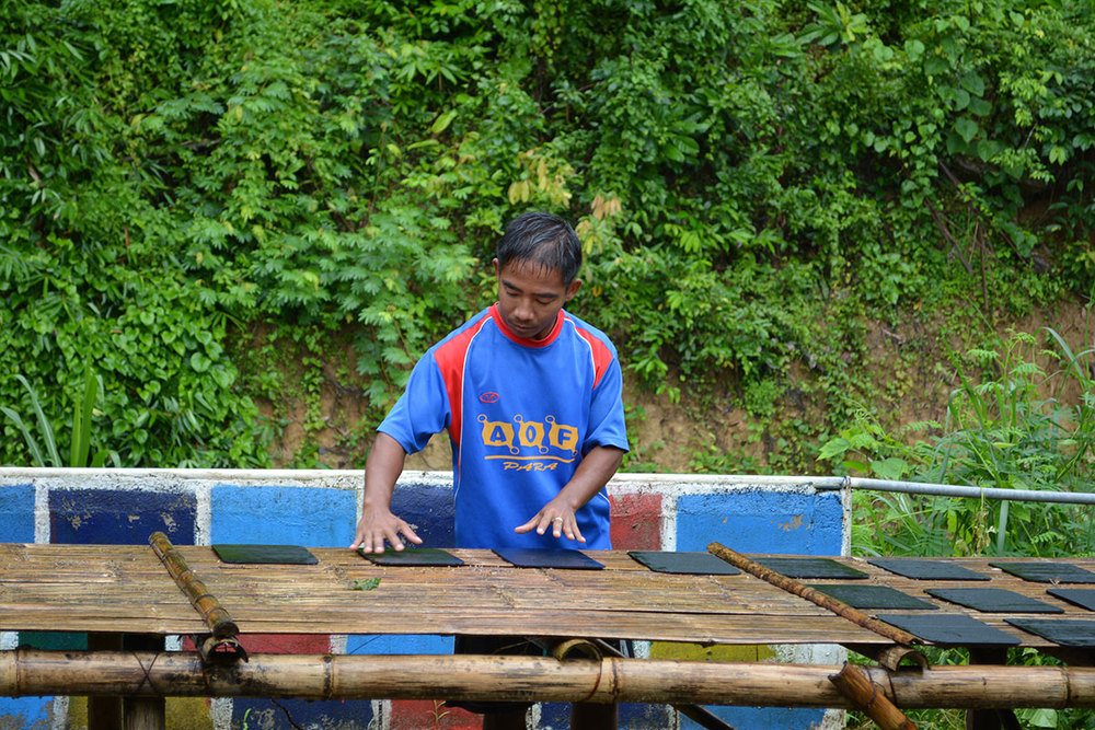 Daeng setting up the material study for another day in the rain.