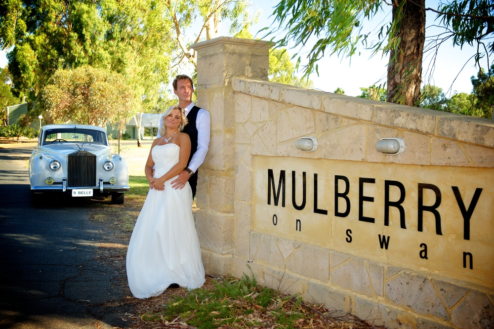 Bridal couple stand in front of one of Belle Classic's cars at Mulberry on Swan, Swan Valley