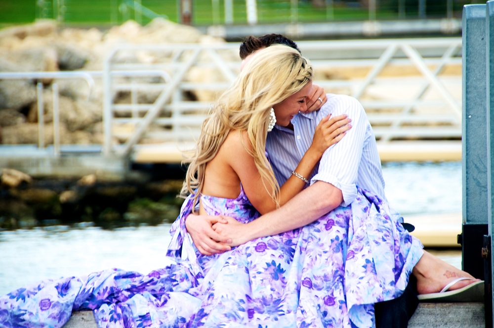 A couple cuddle at Hillarys boat harbour during their engagement photos