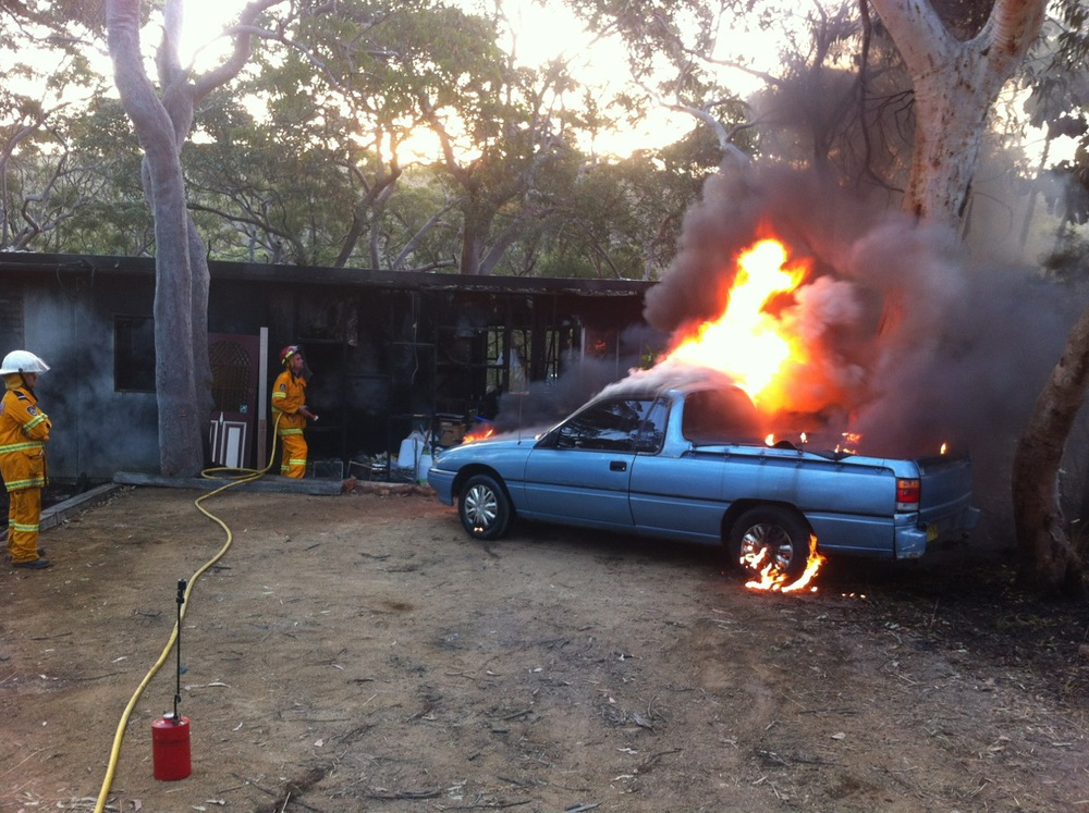 Burning car with rural bush fire volunteers
