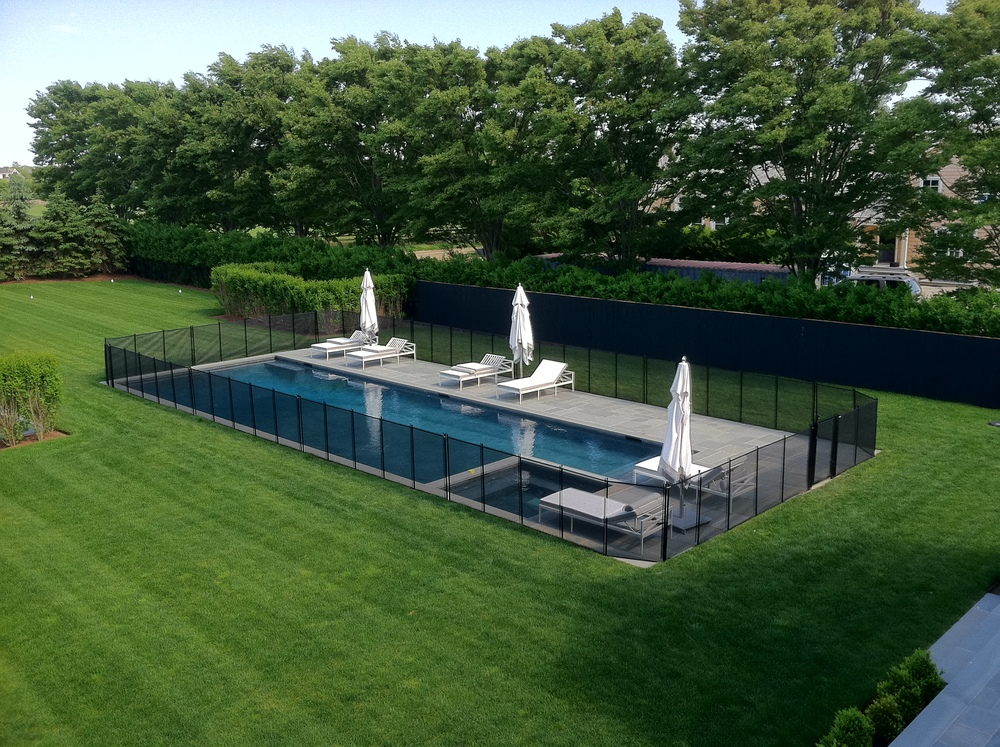 Mesh pool fence installed in soil