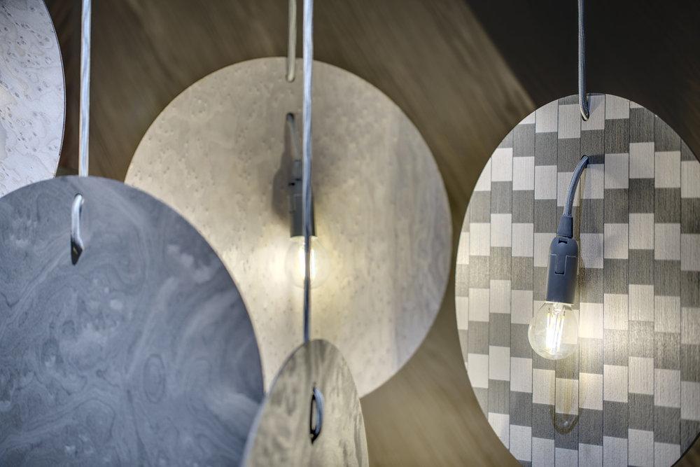 Дизайнер Иван Войтович создал светильник оригинальной конструкции, состоящий из аллюминиевых кругов, шпонированных с обеих сторон. Иван один из первых дизайнеров в мире, который использовал в своем предмете шпон шведской дизайн-группы FRONT:  ALPI Drapery Wood .