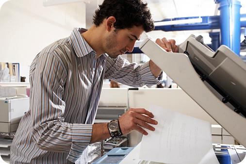 Man leaning placing a sheet a paper over the copy machine.