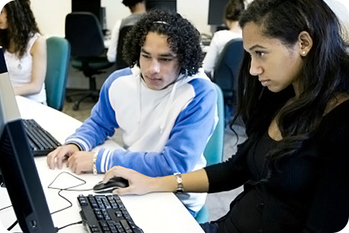 Two students (male and female) are sitting down working on an assignment at their computers. The female student is focused looking at her computer screen, while the male student is leaning over to view  her work on the computer.