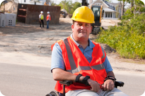 Man on a wheelchair  wearing his construction uniform and hat at a construction site
