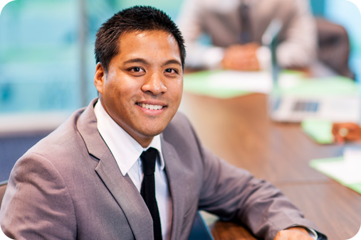 Man in a corporate suit sitting down during a board meeting and smiling at the camera.