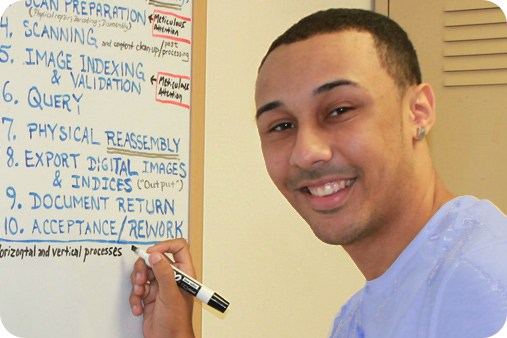Male student writing on the board and smiling at the camera.