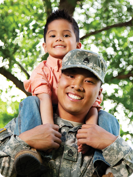 Male soldier in uniform holding his son over his head. Both are happy playing outside. Green trees can be seen in the background.