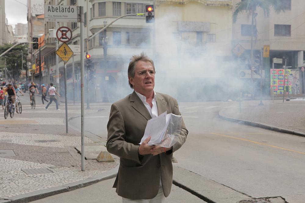 Largo do Paissandu, 16hs. Cidadão caminha. Ao fundo, nuvem de gás lacrimogêneo.