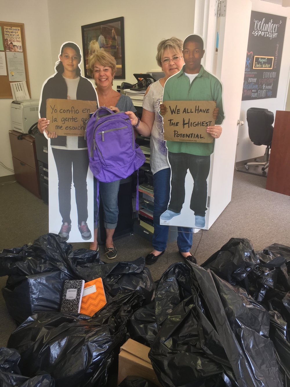 Volunteer Coordinator Margaret Curreri accepts school supply donations from Jean Dingman of the Illuminations Club at Four Seasons at Great Notch.