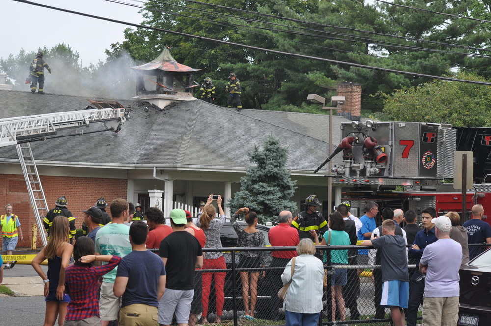 A crowd gathers across from 30 Prospect Street in the Huntington village Saturday, where firefighters extinguish a blaze at approximately 4 p.m.