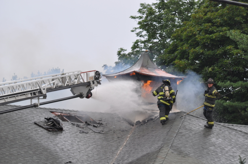 Fire-fighters douse flames shooting out of the building's cupola. Police said Tuesday they believe arson was the cause of the fire.