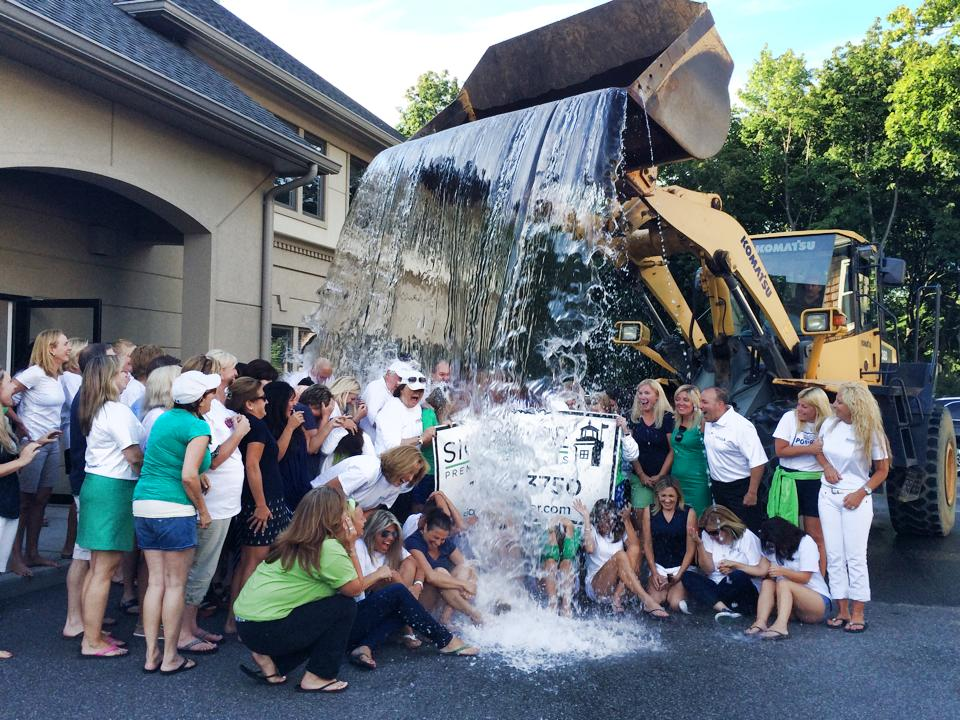 Signature Premier Properties agents and staff took the ice bucket challenge using a payloader's bucket to deliver the dousing at its Huntington office, raising over $6,000.